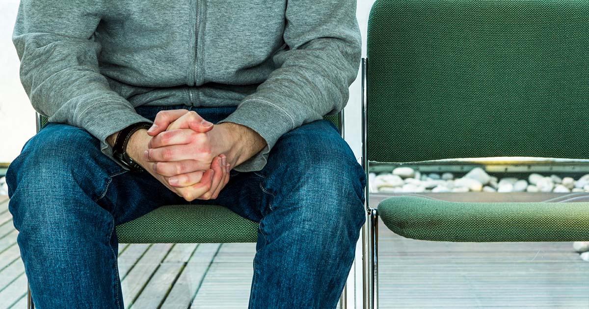 Anxious man sitting with hands clenched in waiting room