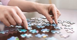 Elderly woman hands doing jigsaw puzzle at home