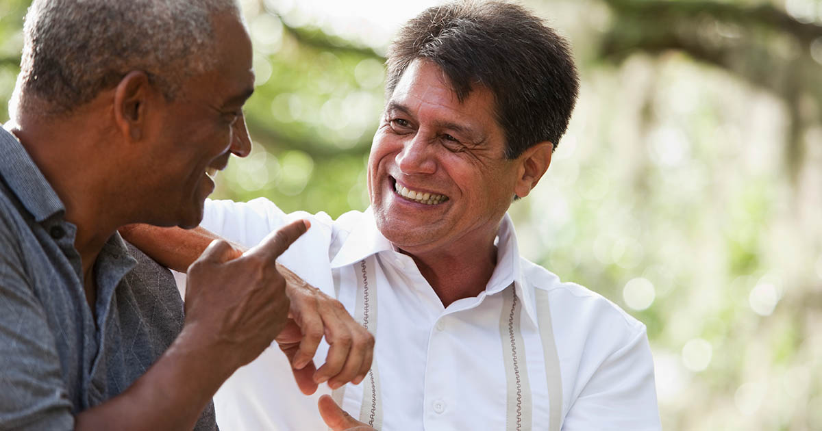 Two men laughing and having an enjoyable conversation outside