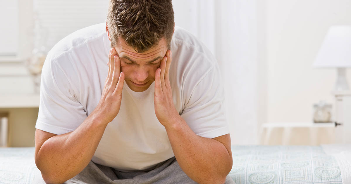 Exhausted man has his head in his hands