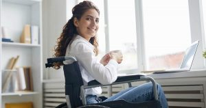 Woman in wheelchair sipping on a cup of coffee