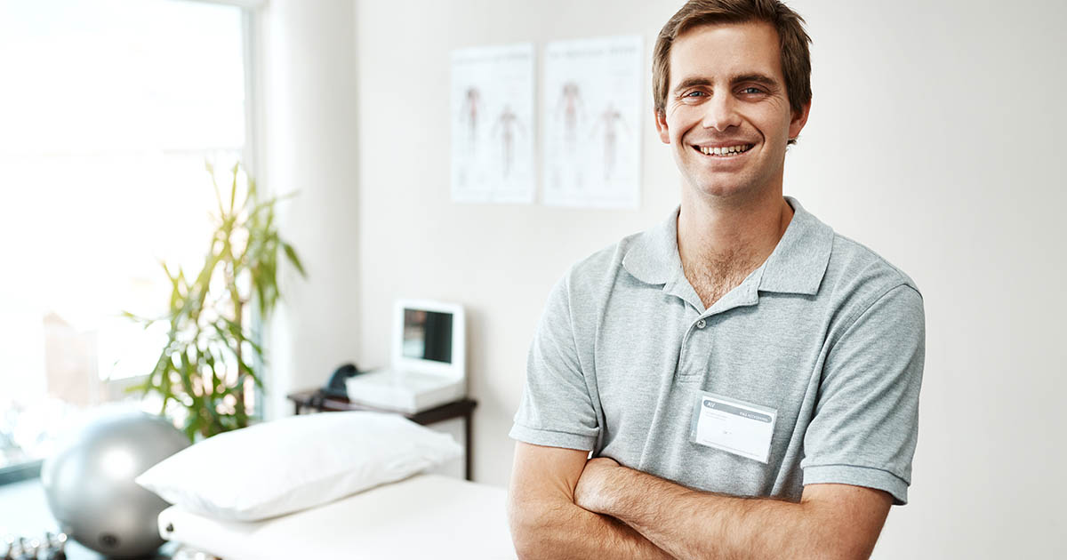 Chiropractor standing with his arms folded inside of his office