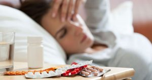 Woman lying in bed with cold medication on a nightstand in the foreground