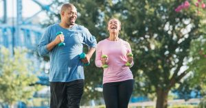 Couple running together in park, laughing