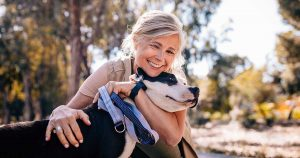Smiling woman hugging and snuggling her dog