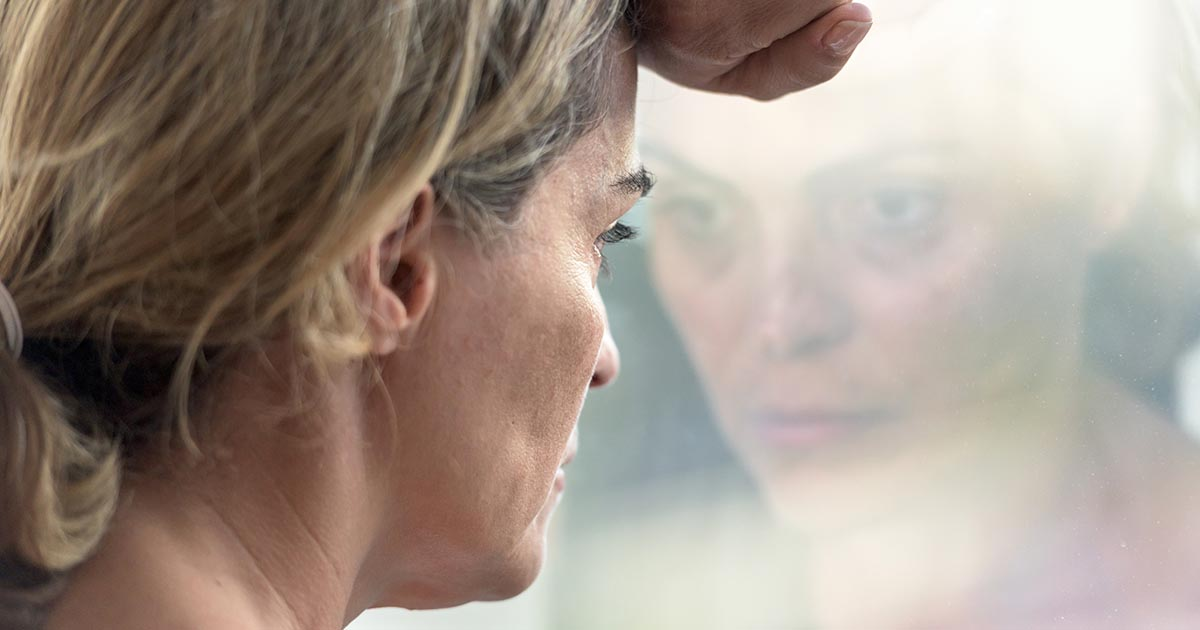 Pensive woman looking through a window