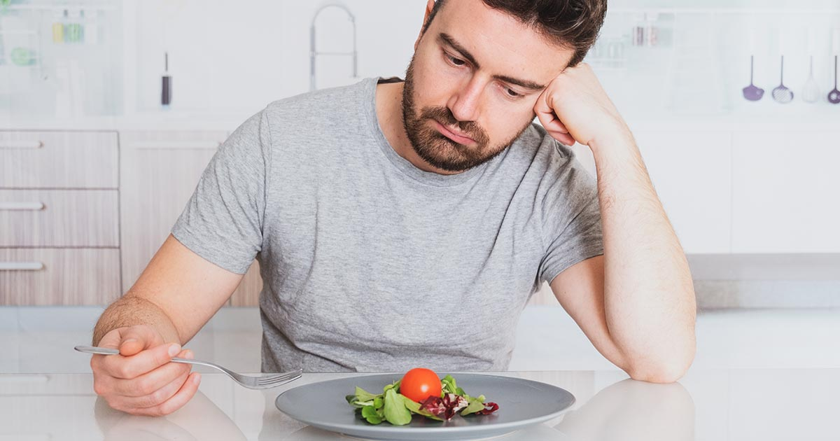 Disappointed man looking at his salad