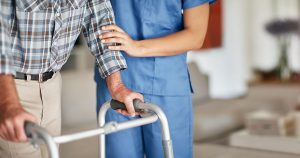 Nurse assisting her elderly patient who's using a walker for support