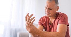 Mature man suffering from hand pain at home while sitting on sofa