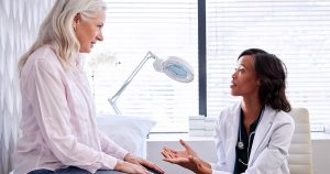 Mature woman listening to her doctor speak