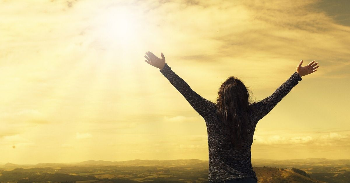 a woman happily watching a sunrise and staying positive